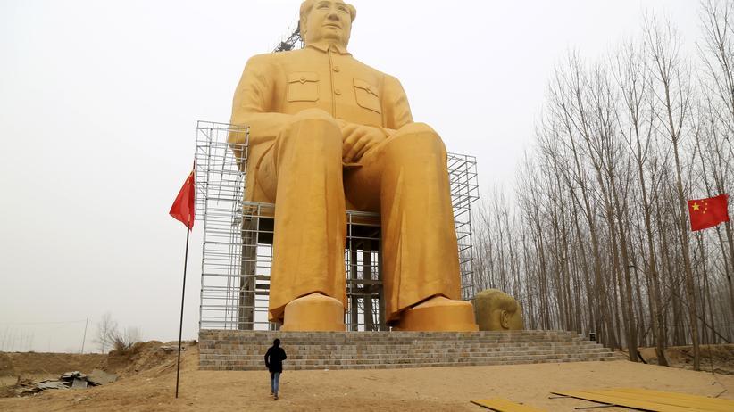 """China: Eine gigantische Statue des Staatsgründers und Revolutionsführers Mao Zedong zwischen Feldern eines kleinen Dorfs in der Provinz Henan. Mao hatte einst auch schon einmal den """"Großen Sprung"""" angekündigt, von der Agrarwirtschaft in die Industrie. Er kostete Millionen das Leben."""