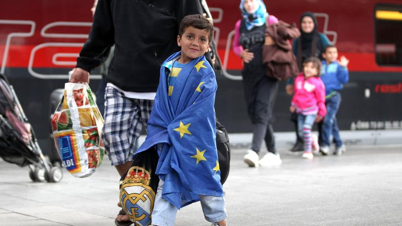 Demografie: Ein Junge in einer EU-Flagge bei seiner Ankunft im Münchner Hauptbahnhof im vergangenen September