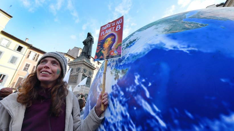 Klimaschutz: A woman holds a placard reading 'There is No Planet B' at Piazza Campo di Fiori during a rally calling for action on climate change on November 29, 2015 in Rome a day before the launch of the COP21 conference in Paris. Some 150 leaders including US President Barack Obama, China's Xi Jinping, India's Narendra Modi and Russia's Vladimir Putin will attend the start of the UN conference Monday, tasked with reaching the first truly universal climate pact. The goal is to limit average global warming to two degrees Celsius (3.6 degrees Fahrenheit), perhaps less, over pre-Industrial Revolution levels by curbing fossil fuel emissions blamed for climate change. AFP PHOTO / TIZIANA FABI / AFP / TIZIANA FABI (Photo credit should read TIZIANA FABI/AFP/Getty Images)