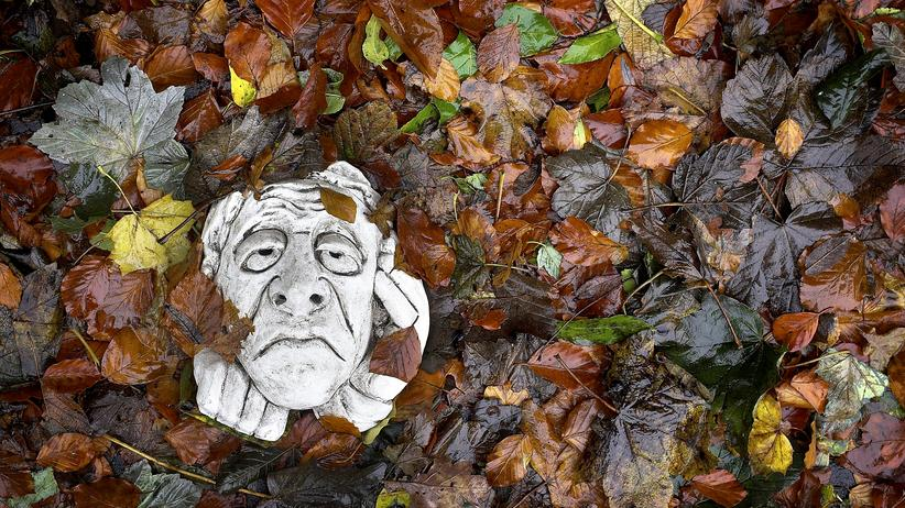 """WHO-Bericht: GLASGOW, UNITED KINGDOM - OCTOBER 12: An ornamental garden gargoyle sits amongst falling leaves as autumn descends and people start to suffer from Seasonal affective disorder. October 12 2005 in Glasgow, Scotland. Seasonal affective disorder (SAD), or winter depression, is a mood disorder related to the change in the seasons and the resulting reduction of exposure to daylight. The end of British Summer time, when clocks go back one hour at the end of October, will see most people making their daily commute in darkness both ways. With winter nights stretching to 19 hours in the UK, and Scotland's often inclement weather, it is estimated that the """"Winter Blues"""" can affect up to 20% of the population. (Photo by Christopher Furlong/Getty Images)"""