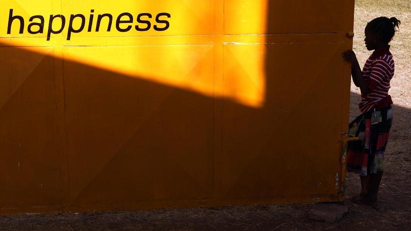 Ein kleines Mädchen steht in Kenia vor einer Werbetafel.