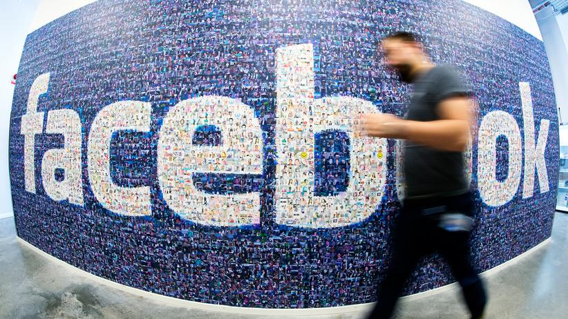 Facebook: This picture taken with a fisheye lens shows a man walks past a big logo created from pictures of Facebook users worldwide in the company's Data Center, its first outside the US on November 7, 2013 in Lulea, in Swedish Lapland.