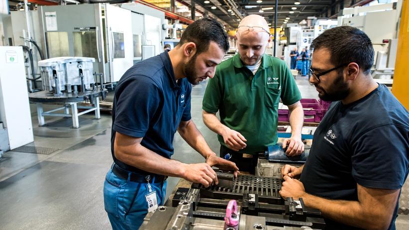 Integration: Ein syrischer Flüchtling mit zwei Kollegen in der BMW-Fabrik München