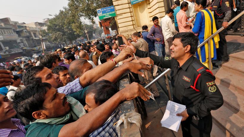 Indien: Alle wollen noch schnell ihr Geld tauschen, ehe sie Ersparnisse verlieren: Die indischen Banken mussten ihre Sicherheitspersonal aufstocken, um den Andrang der Menschen in ihren Filialen bewältigen zu können.