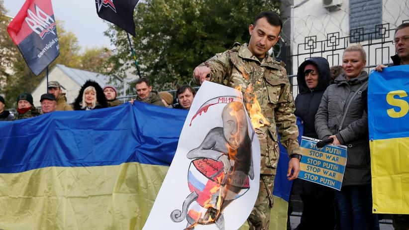 Ukraine: Protest gegen Wladimir Putin: Am 14. Oktober 2016, dem Tag der Verteidiger der Ukraine, verbrennt ein Aktivist vor der russischen Botschaft in Kiew ein Poster mit dem Bild des russischen Präsidenten. Die Ukraine reformiert sich und will liberaler, westlicher werden – Putin dürfte das nicht gefallen.