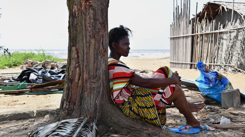 Klimawandel: In Grand-Lahou, einer Stadt der Elfenbeinküste, rastet eine Frau unter einem Baum. Das Bild entstand im November 2016, nachdem das Meer die halbe Stadt überflutet hatte. Eine Folge des Klimawandels?