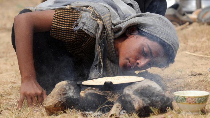 Energie: Eine Pakistanerin bereitet Brot über einem Feuer.