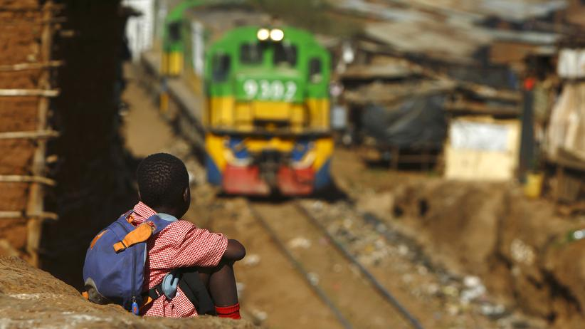 Elektrizität: Ein Kind beobachtet einen Zug, der durch den Slum Kibera in Kenias Hauptstadt Nairobi fährt.
