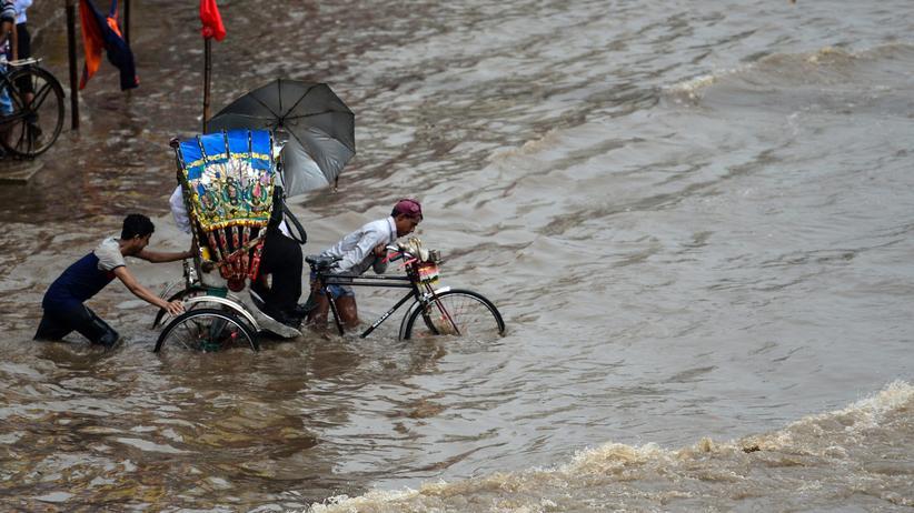 Brot für die Welt: Ein Rikscha-Fahrer in Dhaka zieht sein Gefährt mit Fahrgast durch die Flut – aufgenommen am 26. Juli 2017.