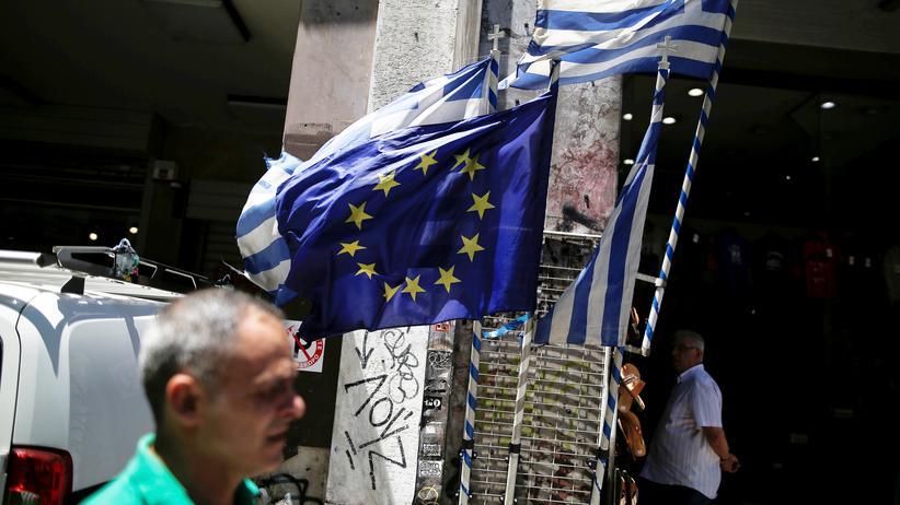 Euro-Krise: Eine griechische und eine Flagge der EU vor einem Geschäft in Athen, Griechenland