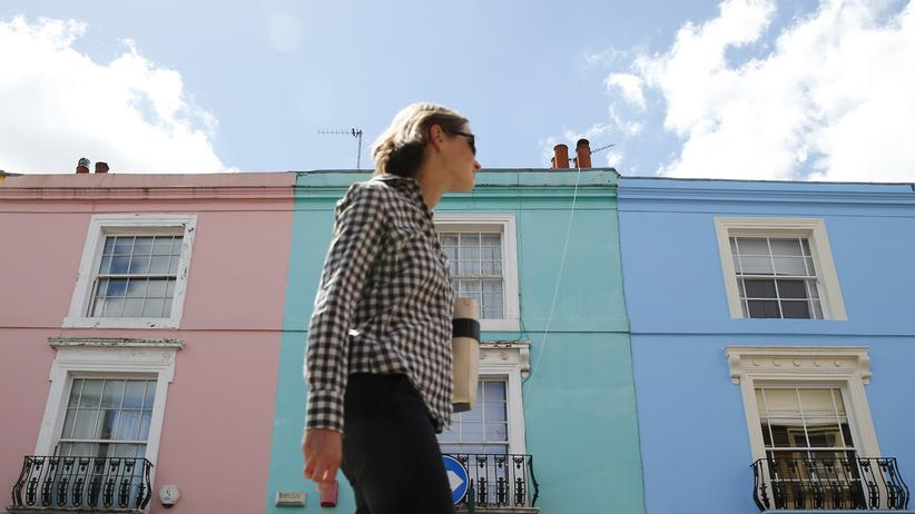 Großbritannien: Passantin vor einer Londoner Häuserreihe