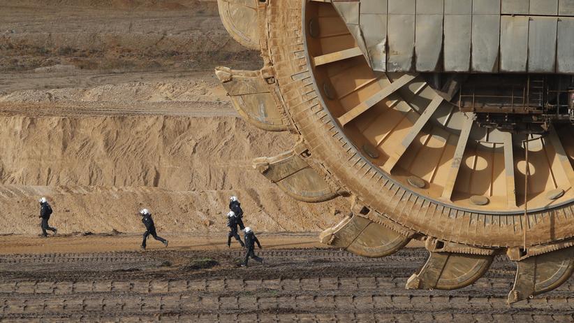 Energiepolitik: Anfang November im Tagebau Garzweiler: Während einer Demonstration gegen den Tagebau rennen Polizisten an einem Braunkohlebagger vorbei.
