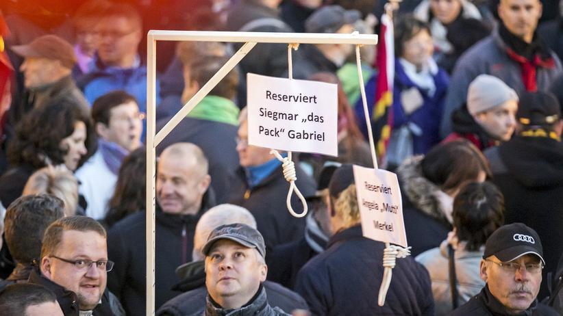 Demonstranten von Pegida halten Galgen mit Politikernamen bei einer Kundgebung in Dresden im Oktober 2015 hoch.
