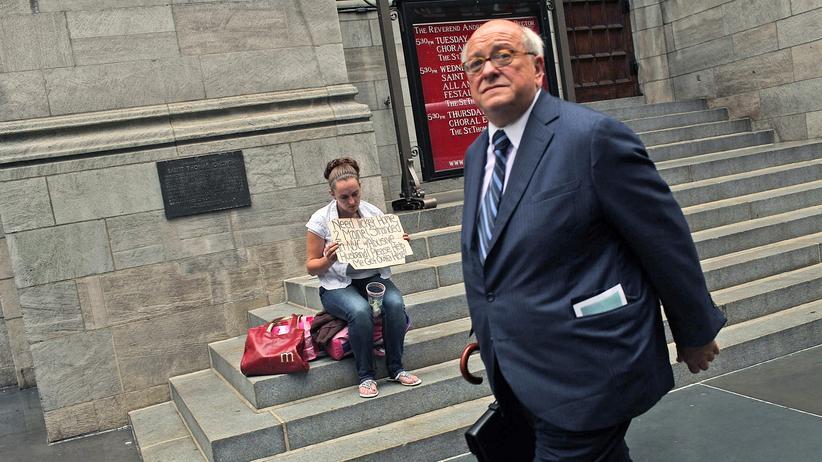 Ungleichheit: Ungleiche Verhältnisse: ein Geschäftsmann und eine Frau, die um Geld bittet, in New York (Archivfoto)