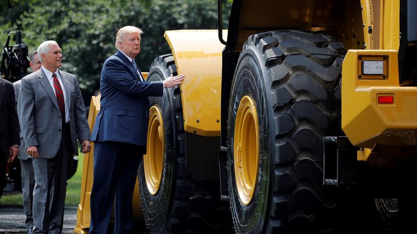 """US-Handelspolitik: US-Präsident Donald Trump und sein Vize Mike Pence bewundern ein Fahrzeug der Marke Caterpillar, aufgenommen auf einer """"Made in America""""-Ausstellung im vergangenen Sommer im Weißen Haus."""