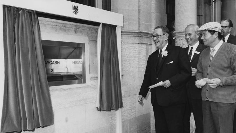 Banken: 27. Juni 1967 in Enfield nördlich von London: Vizebankdirektor Sir Thomas Bland (links) von der Barclays-Bank in London eröffnete gemeinsam mit dem Chef des Banknotenherstellers De La Rue, Sir Arthur Norman, den ersten Geldautomaten der Welt. Auch dabei war der Schauspieler Reg Varney (mit Mütze).