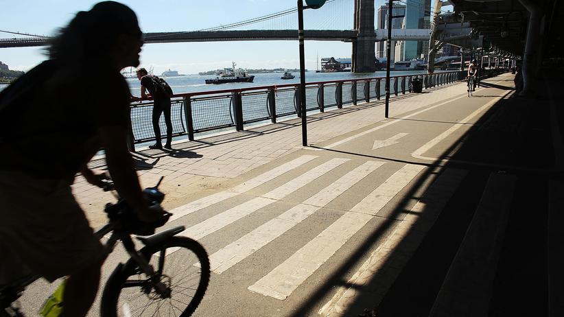 Fahrradverleih: Eine Radfahrerin am East River in New York