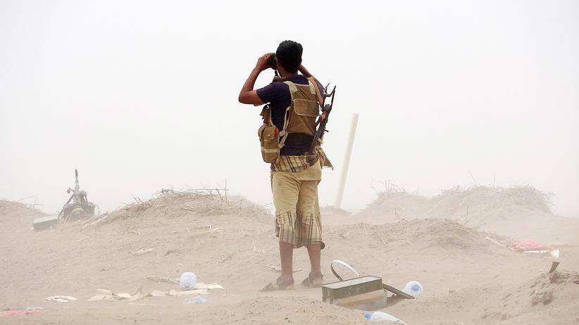 Jemen: Ein regierungstreuer jeminitischer Soldat schaut mit einem Fernglas in Richtung Hudeida