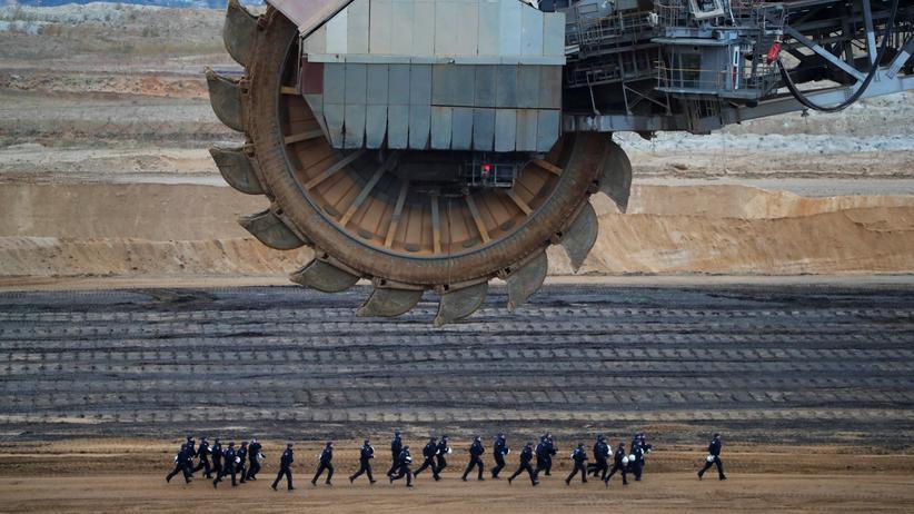 Klimapolitik: Polizisten rennen im Tagebau von Garzweiler, Nordrhein-Westfalen, an einem Braunkohlebagger vorbei. Das Bild entstand im November 2017, als Aktivistinnen und Aktivisten in die Kohlegrube eindrangen.
