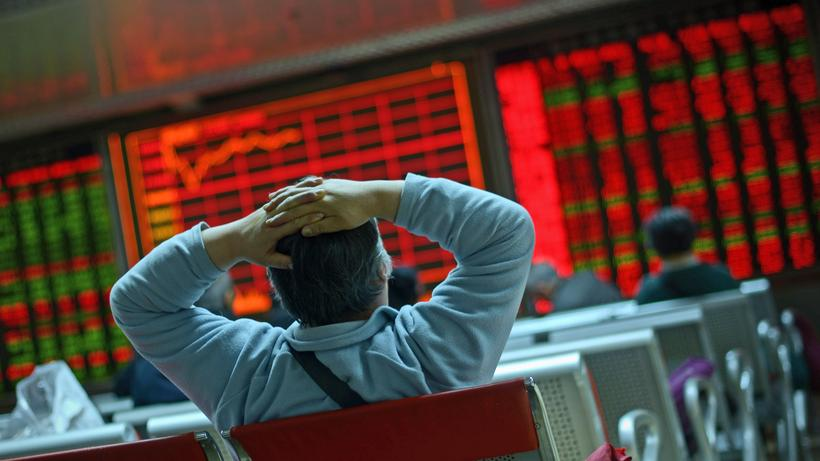 Financial Crisis: An investor looks at screens showing stock market movements at a securities company in Beijing.