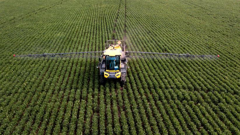 Glyphosat: Einsatz von Pestiziden auf einem Sojafeld: Der Dax-Konzern Bayer ist inzwischen mit rund 13.400 US-Klagen wegen des Unkrautvernichters Roundup konfrontiert.