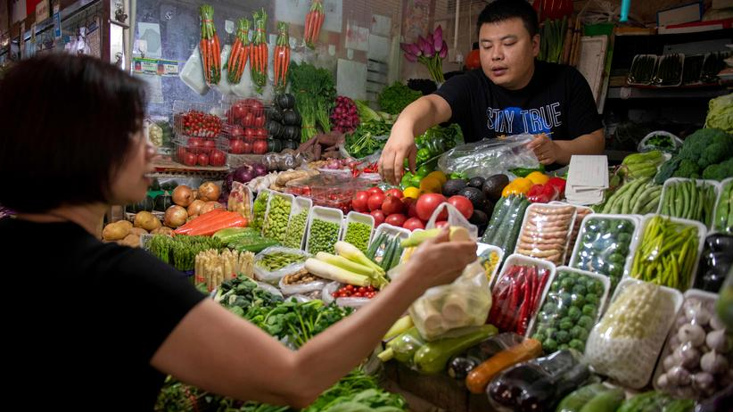 Handelsstreit: Ein Gemüseverkäufer auf einem Markt in Peking preist seine Produkte an.