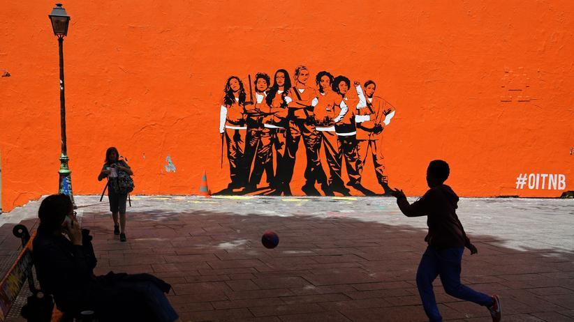 Streamingdienst: In Paris spielt ein kleiner Junge vor einer Mauer Fußball, die für eine Netflix-Serie wirbt.