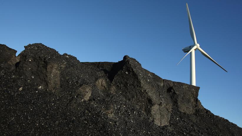 Energiewende: Ein Windrad hinter einem Kohleberg