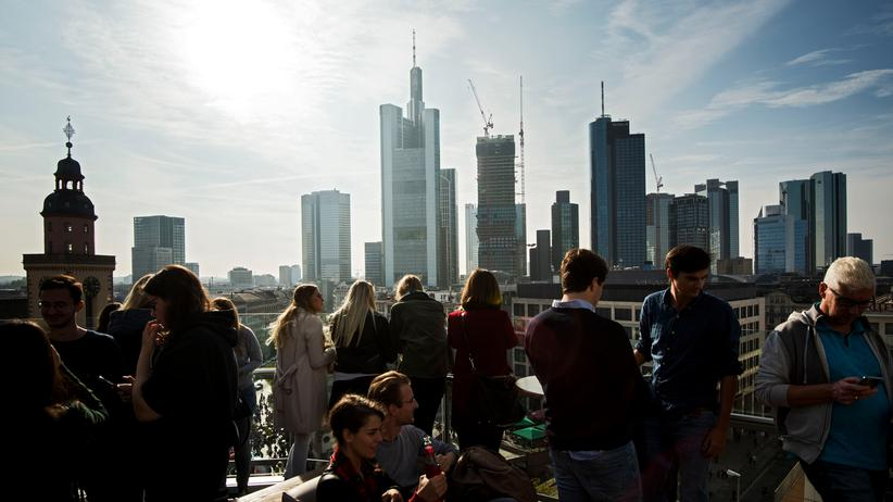 Banken: FRANKFURT AM MAIN, GERMANY - OCTOBER 20: Guests stand at the rooftop of a shopping mall and look at the skyline and the finance district on October 20, 2018 in Frankfurt, Germany. Skyrocketing costs for housing have become a major issue in cities across Germany, with local government scrambling to find policy solutions. Frankfurt in particular is already attracting wealthy newcomers as the city becomes an alternative for companies in the financial sphere relocating from Brexit-afflicted London. In other cities, especially Berlin, foreign investors, including from China, are parking their money in luxury apartment purchases. (Photo by Thomas Lohnes/Getty Images)