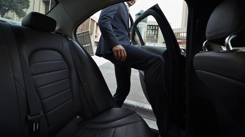 Neue Arbeitsformen: Businessman getting into backseat of exclusive cab