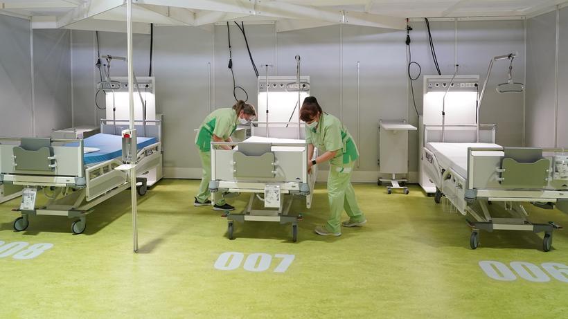 Corona-Pandemie: In der auf dem Berliner Messegelände aufgebauten Corona-Notklinik bereiten Beschäftigte die Betten vor.
