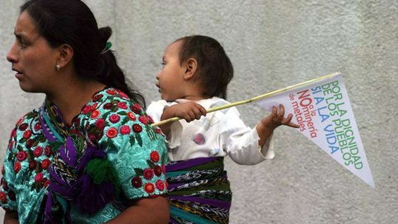 """Edelmetall: Eine Frau protestiert gegen in Guatemala-Stadt gegen Marlin, ihr Kind auf dem Rücken (Archivbild). Auf der Flagge steht: """"Für die Würde der Völker, ja zum Leben und nein zum Metallbergbau"""""""