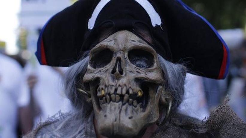 Ein Demonstrant trägt eine Totenschädel-Maske und einen Piratenhut