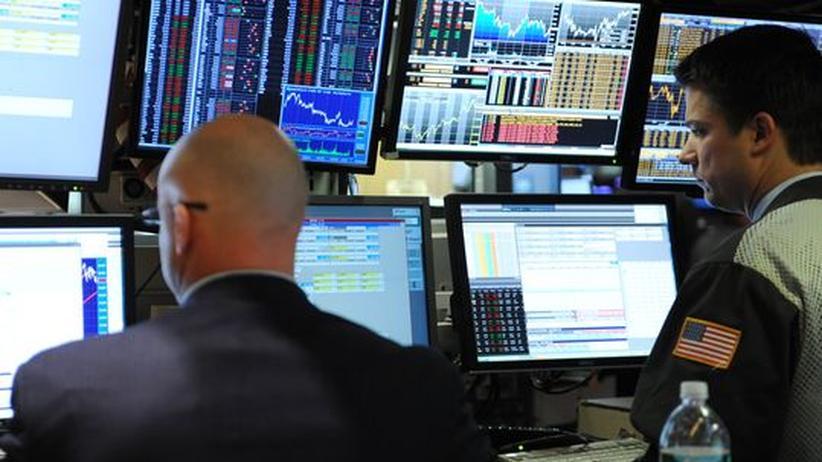 """Finanzmarkt: Sie arbeiten nicht für einen """"Dark Pool"""": Zwei Männer auf dem Parkett der New Yorker Börse beobachten Aktienkurse auf Computermonitoren."""