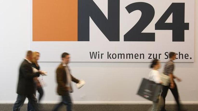 Mitarbeiter laufen an einem Logo des Nachrichtensender N24 vorbei