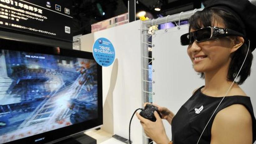 Eine junge Frau präsentiert ein neues 3D-Spiel für die Playstation auf einer Messe in Tokyo