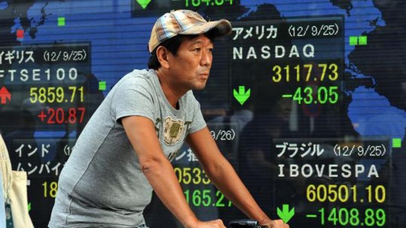 Ostasien: Ein Radfahrer vor Börsenkursen Ende September in Tokio. Anfang Oktober wurde bekannt, dass der Absatz von Toyota in China im Vormonat um 40 Prozent eingebrochen war.