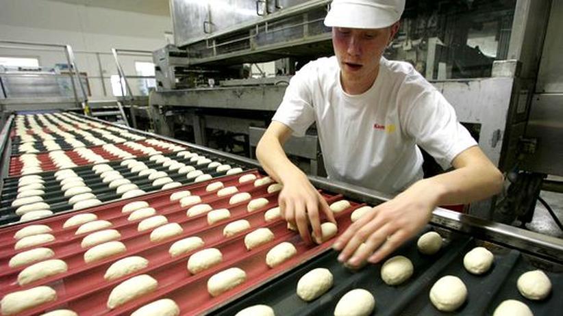 Einzelhandel: Brötchen am Fließband: Ein Mitarbeiter der Großbäckerei Kamps belegt Backbleche mit Teiglingen.