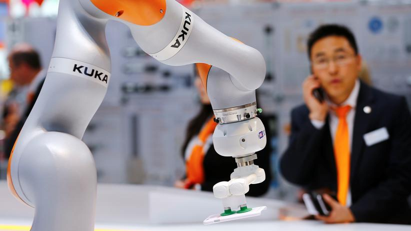 Eine Frau steht vor einem Roboter