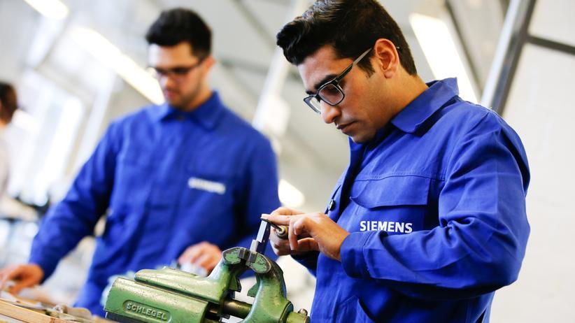 Integration: Flüchtlinge im Blaumann der Siemens AG, wo sie eine Anstellung gefunden haben.