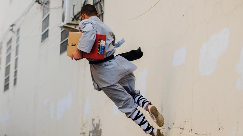 Arbeitsbedingungen in China: Auslieferung goes Martial Arts: Gekleidet in einem Kung-Fu-Kostüm stellt dieser Mann im chinesischen Dengfeng ein Paket von Alibaba zu.