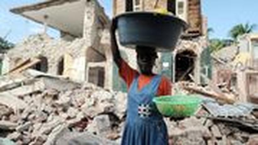 Hinter einer Haitianerin liegen die Wohnhäuser von Jacmel in Trümmern