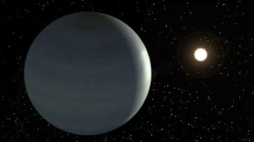 Exoplanet entdeckt: Diese Illustration zeigt den Exoplaneten Corot-9b. Im Hintergrund ist sein Zentralstern zu sehen. Die bläuliche Oberfläche ist angelehnt an das mögliche Vorkommen an Wassermolekülen in der Atmosphäre von Corot-9b