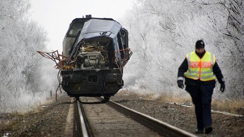 Ein Polizeibeamter geht die eingleisige Bahnstrecke nahe Hordorf ab. Im Hintergrund steht die beschädigte Lok des Güterzuges. Sie kollidierte am 29.01.2011 mit einem Nahverkehrszug, zehn Menschen starben