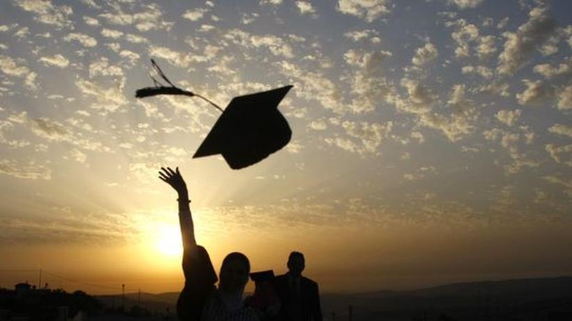Ein Studierender wirft seinen Doktorhut gen Himmel