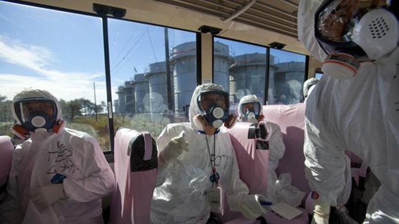 Journalisten und Tepco-Mitarbeiter fahren im November 2011 im Bus an die Reaktorruinen des Atomkraftwerks Fukushima-Daiichi heran.