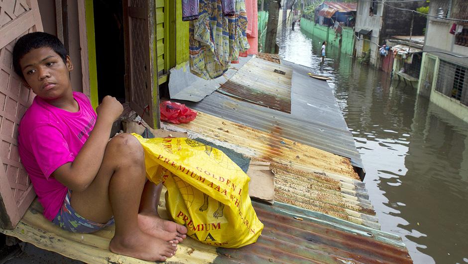 Ein Bewohner Manilas hat sich in einer überfluteten Straße auf einem Dachvorsprung in Sicherheit gebracht.
