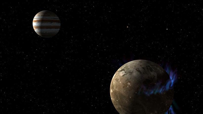 Tanzende Polarlichter umgeben den größten Jupiter-Mond Ganymed (künstlerische Darstellung)