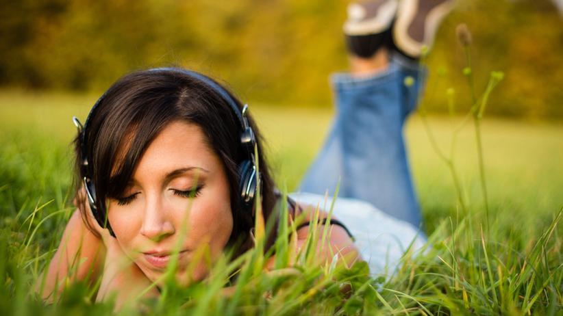 Frau mit Kopfhörern auf einer Wiese