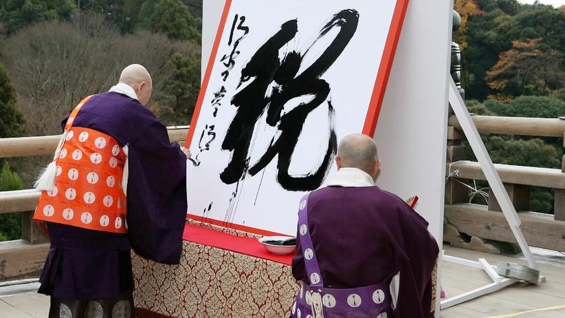 Kanji: Zwei buddhistische Priester haben das Kanji-Schriftzeichen für Steuer auf ein Plakat geschrieben. Im vergangenen Jahr war dies eine Referenz an Japans Schuldenkrise.